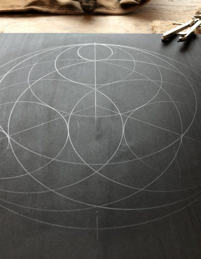 circular geometric pattern drawn on slate