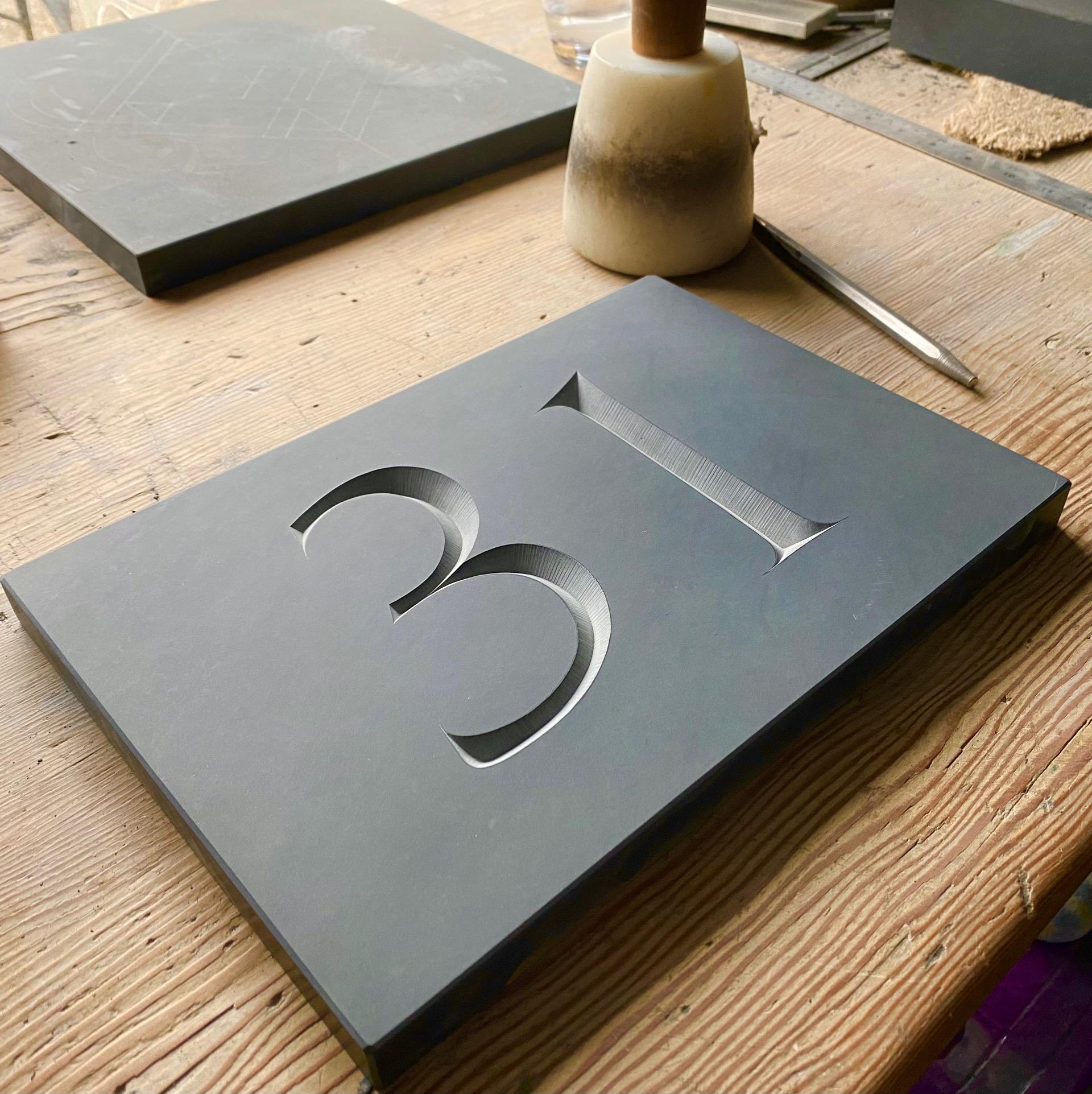Number 31 had carved in dark grey welsh slate by Zoe Wilson