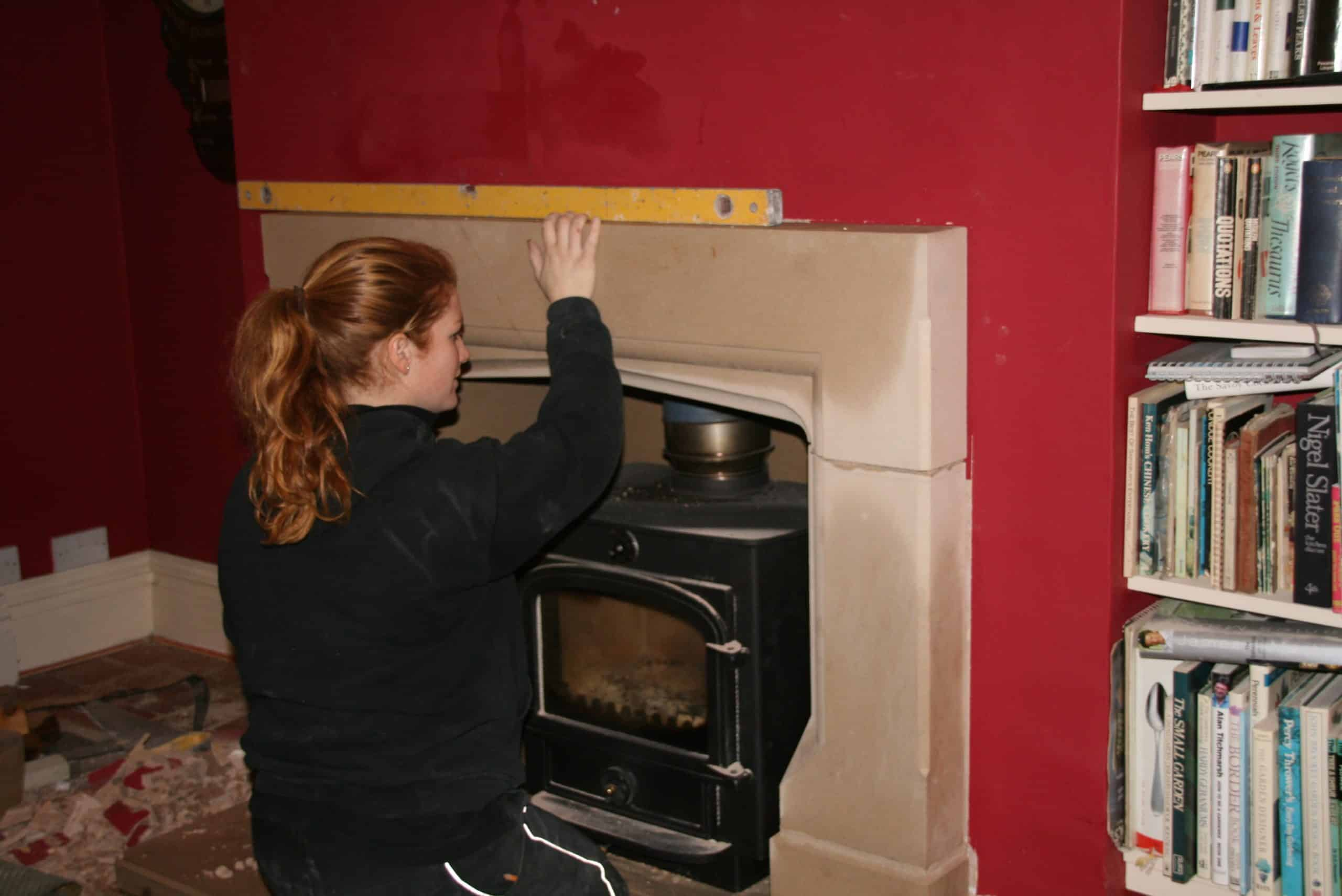 Zoe fixing a fireplace she made into the clients sitting room