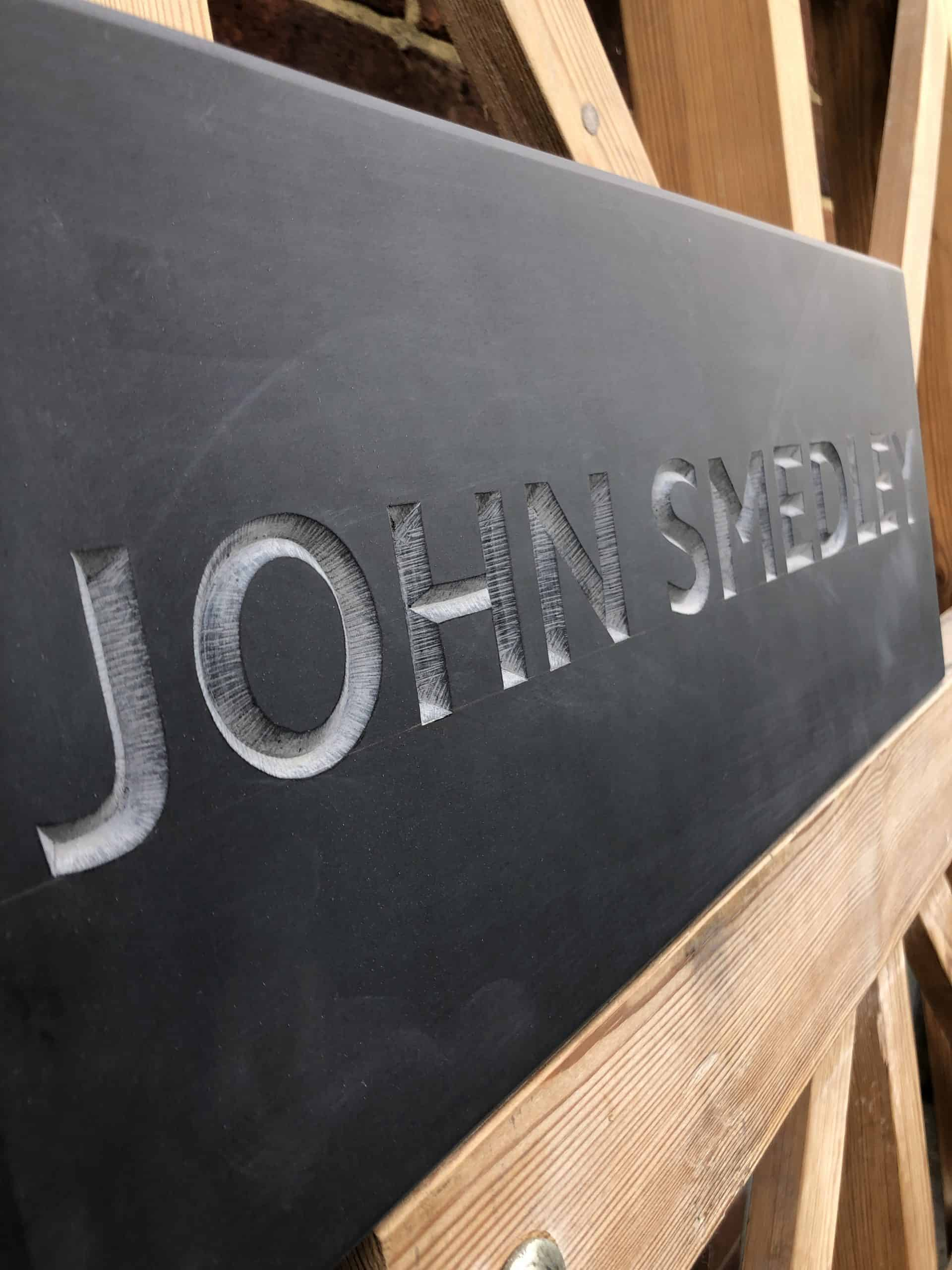 Carved Letters in Welsh Slate saying John Smedley carved by Zoe Wilson