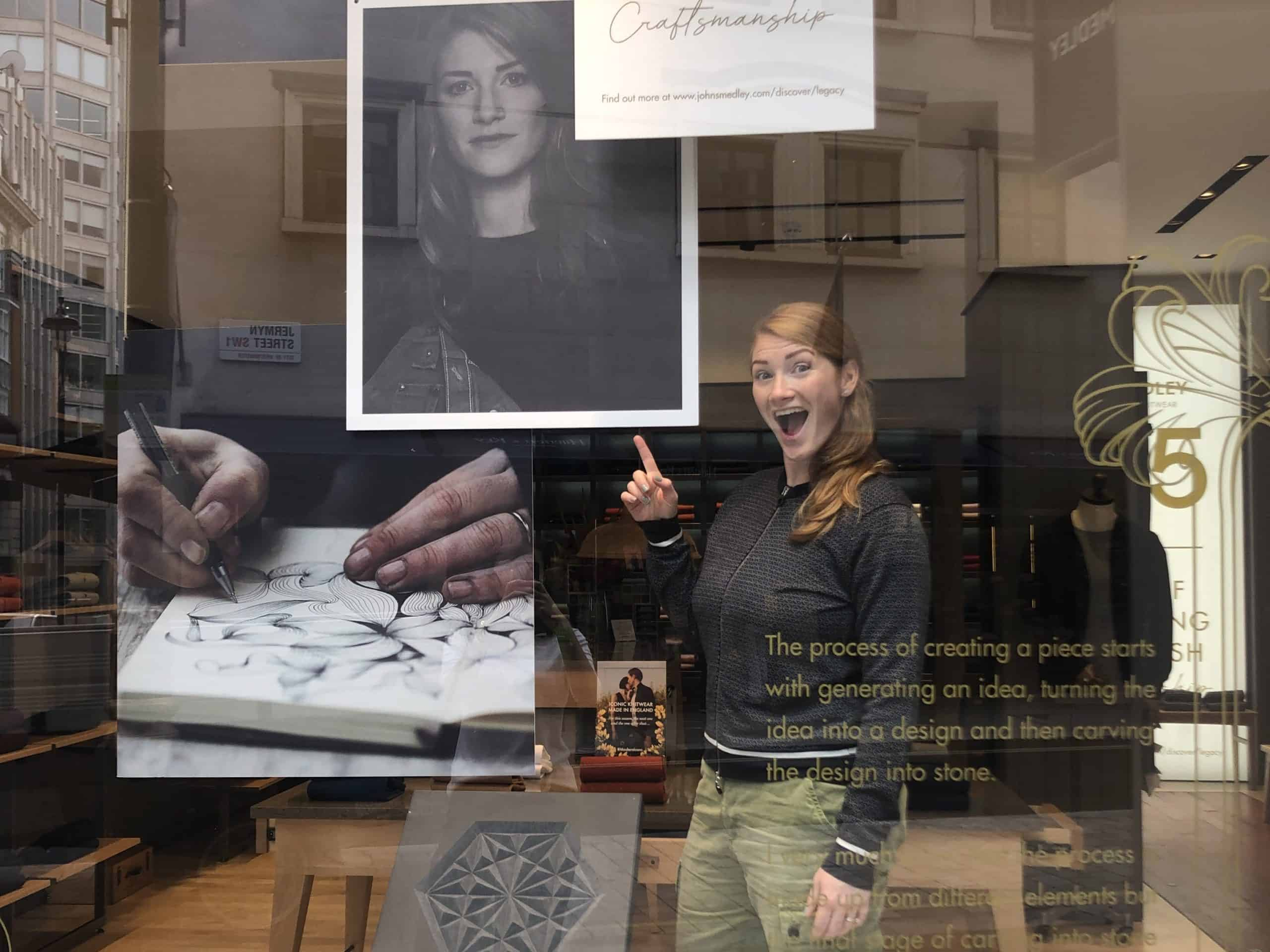 Zoe standing in the window of a John Smedley store in London next to her work.