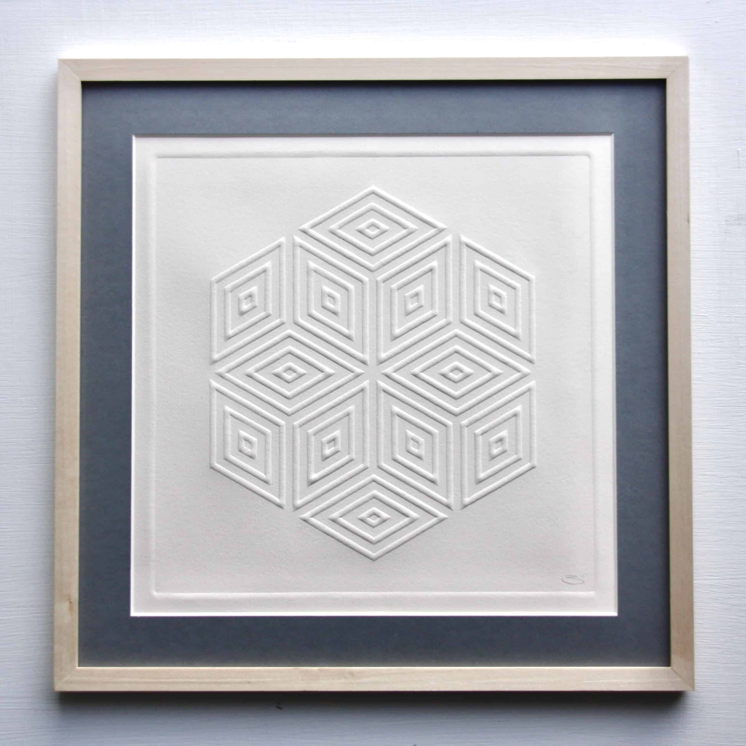 Paper pressed into the stone carving to make a raised embossing. Pattern is a geometric shape based on a diamond