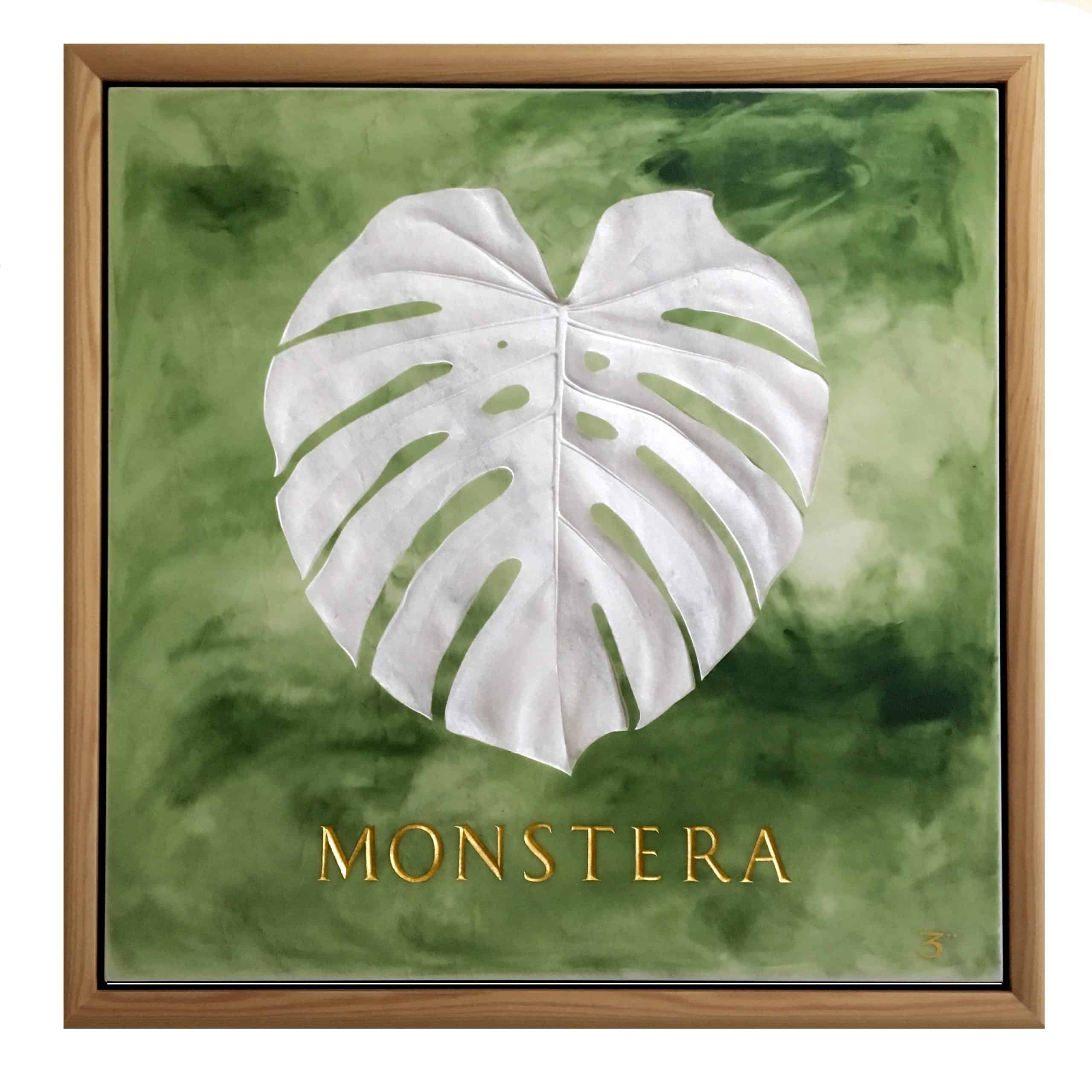 shallow relief carved monstera leaf in white marble with green painted surround