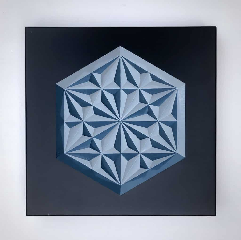 Decorative geometric pattern carved into slate and painted two shades of blue with enamel paint