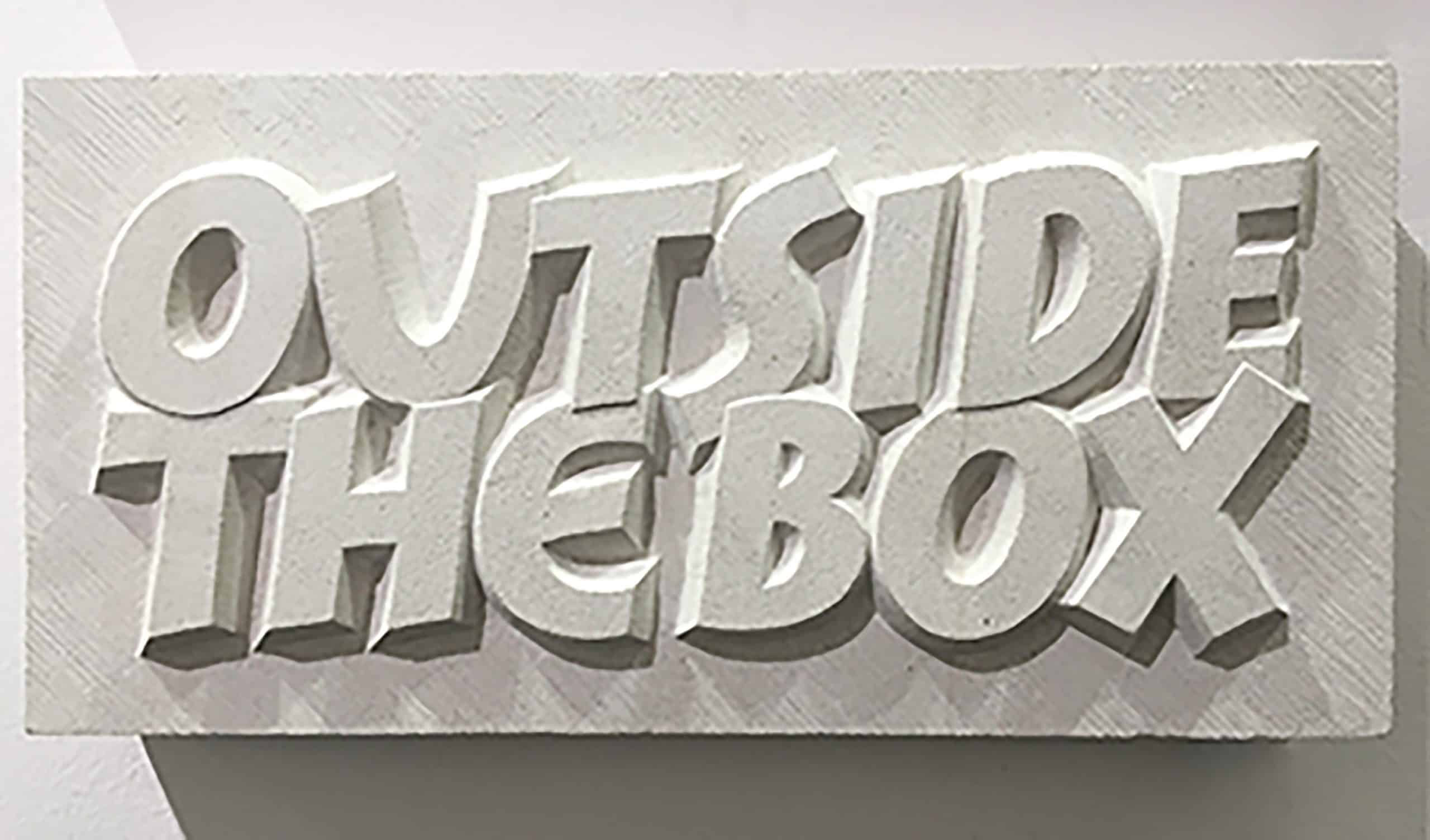 Raised letter carving reading 'Outside the Box' in a buff coloured limestone