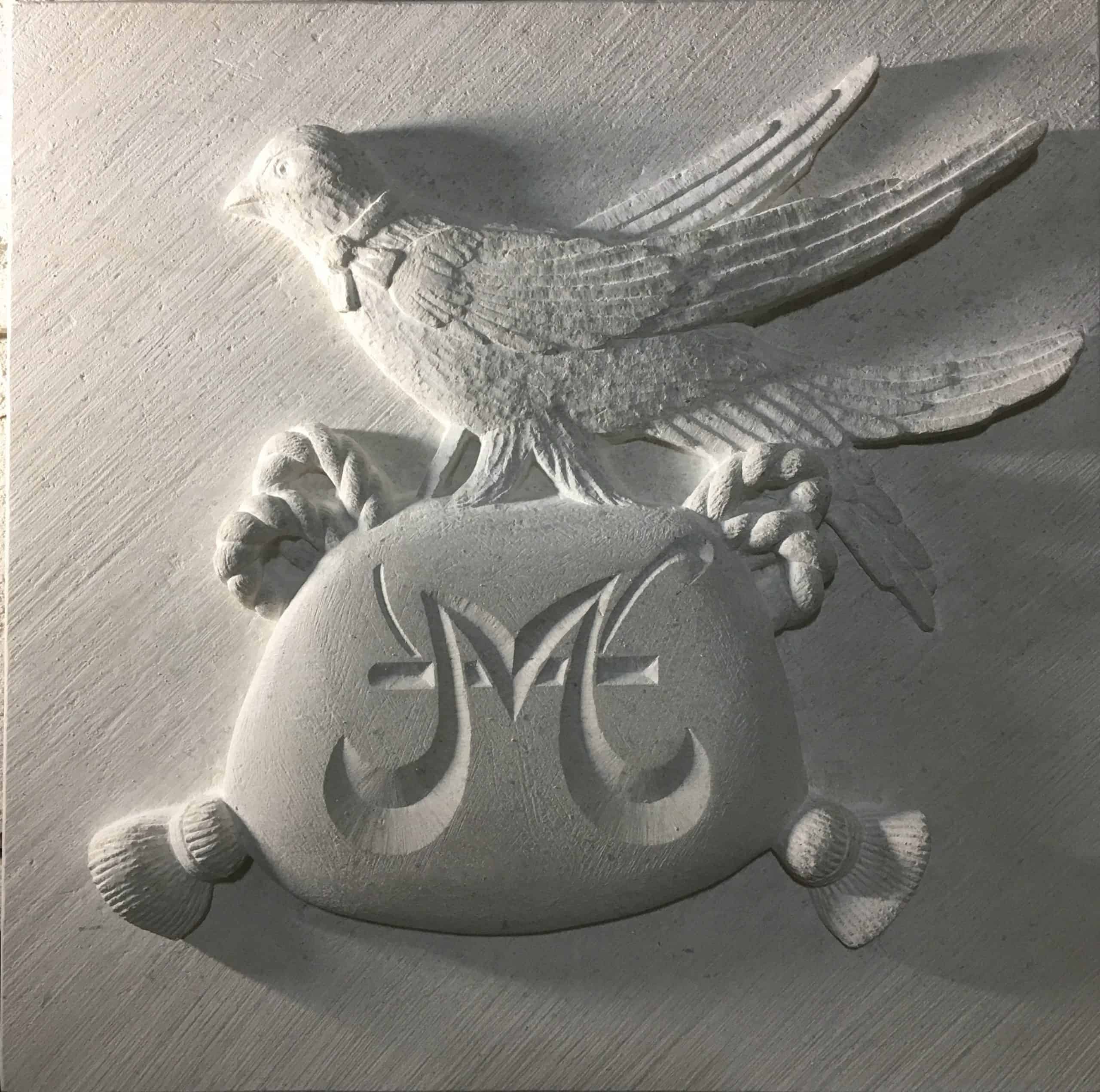 Family crest of a Martlet on top of a purse carved in stone