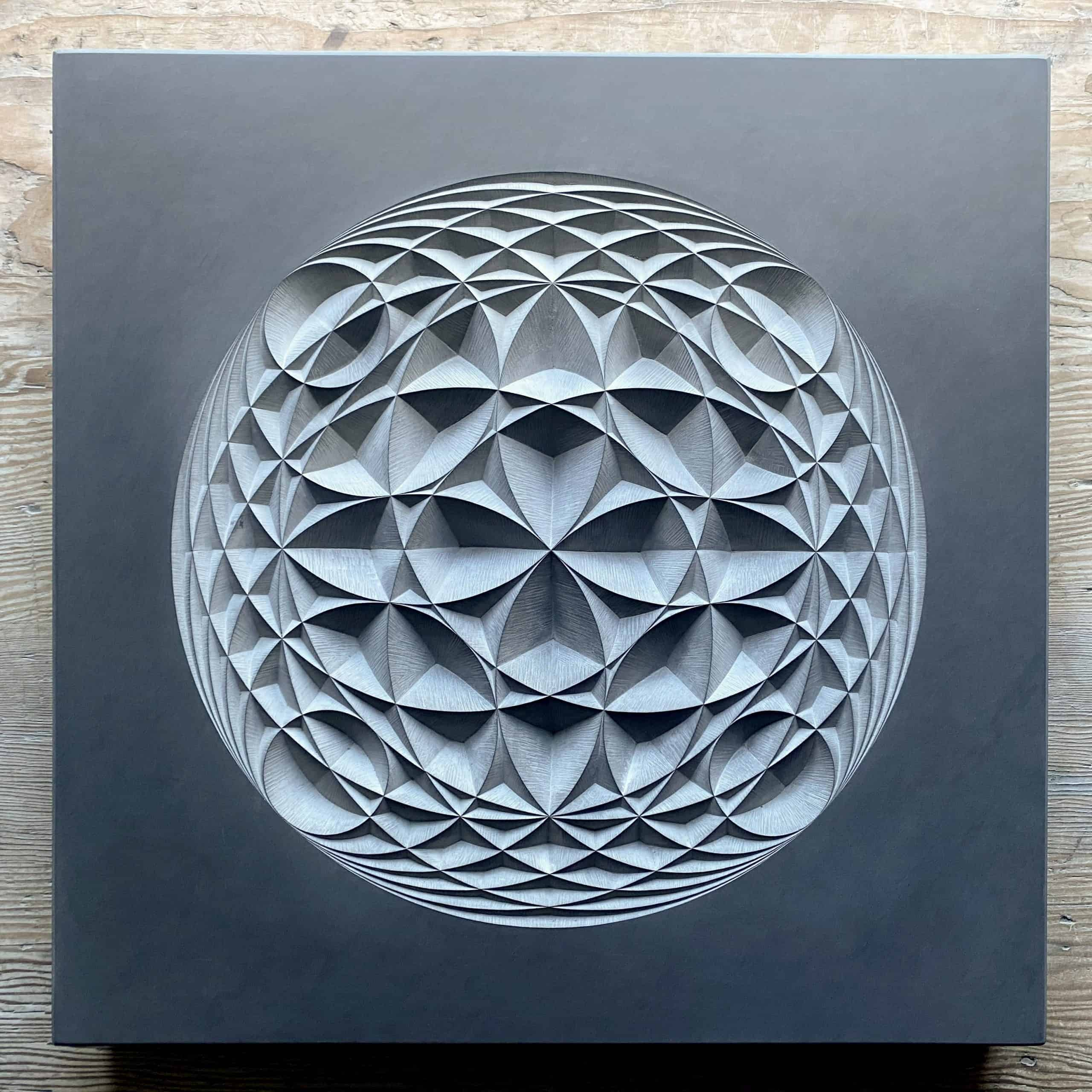 Overlapping circular geometric pattern carving into dark grey slate