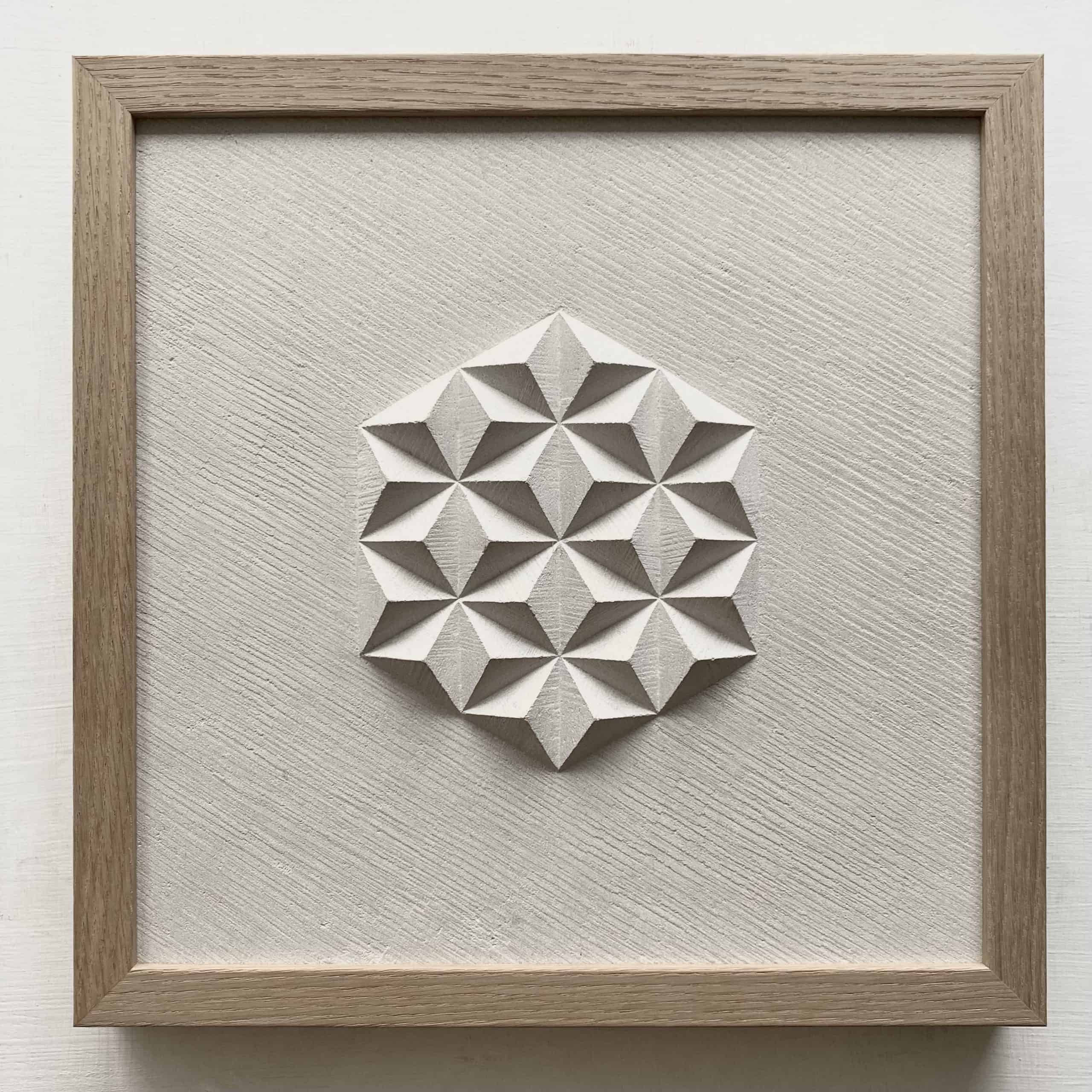 Hand carved geometric pattern which looks like pyramids, in a buff limestone
