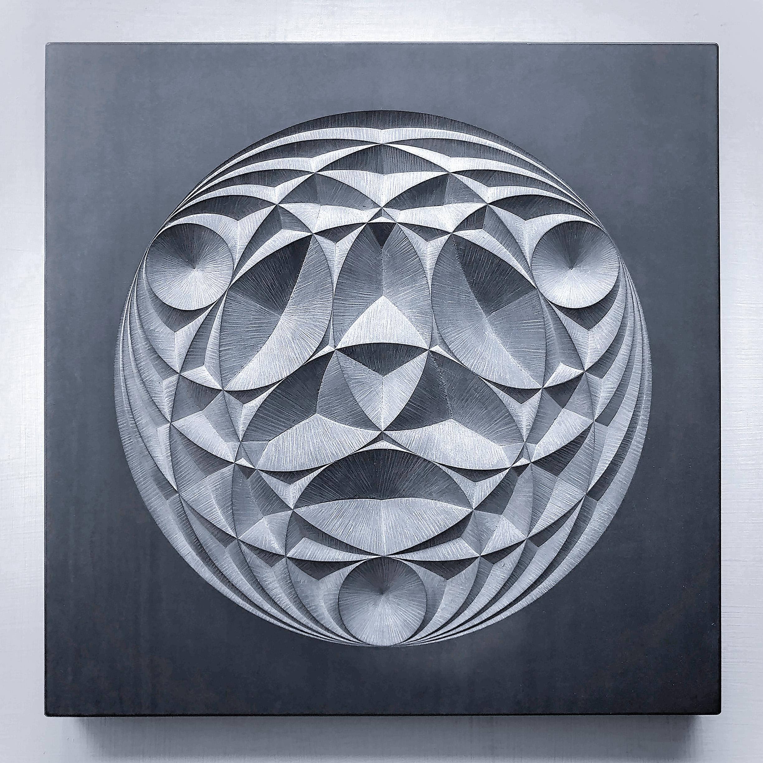 Circular geometric pattern carved into dark grey slate