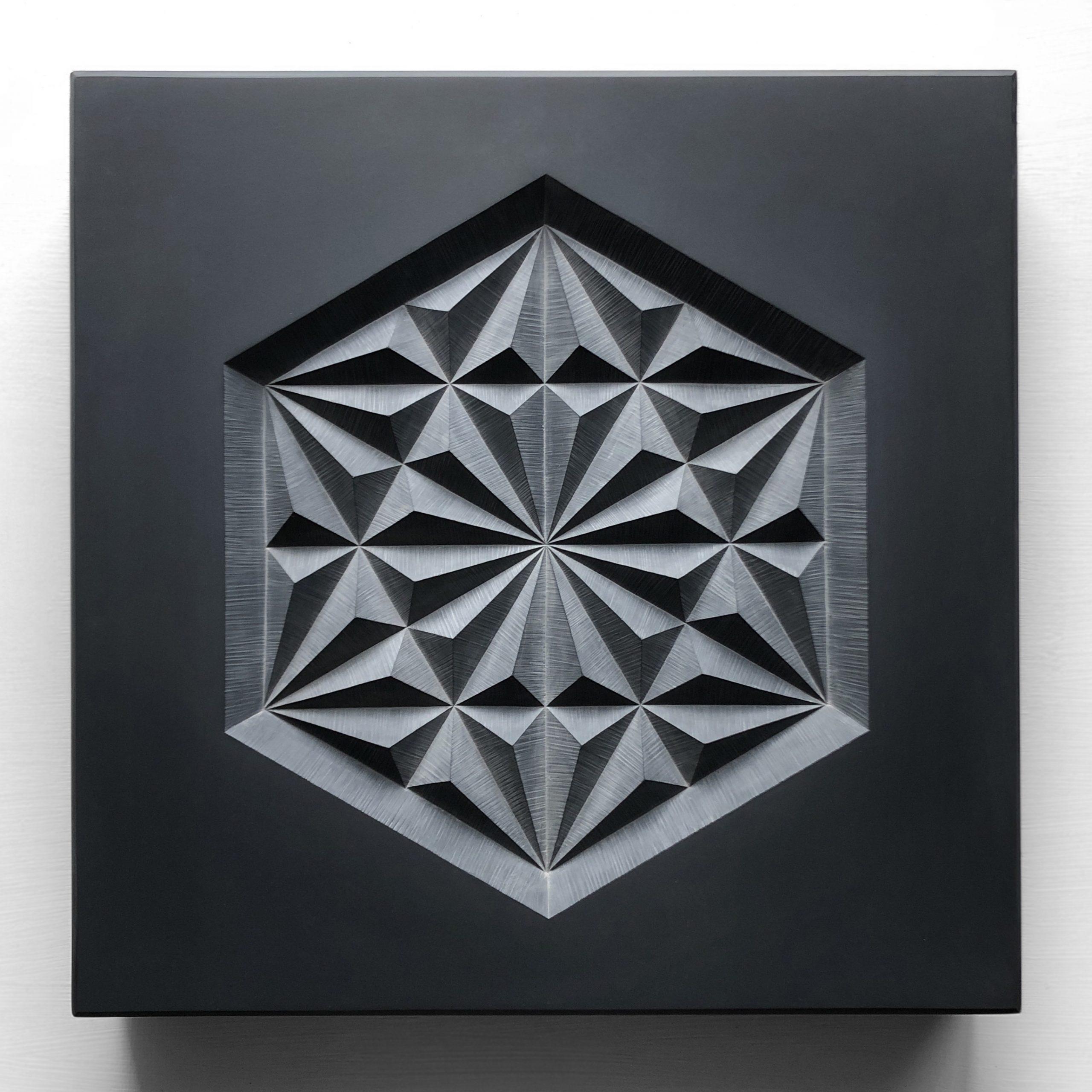 Angular geometric pattern carved into dark grey slate.