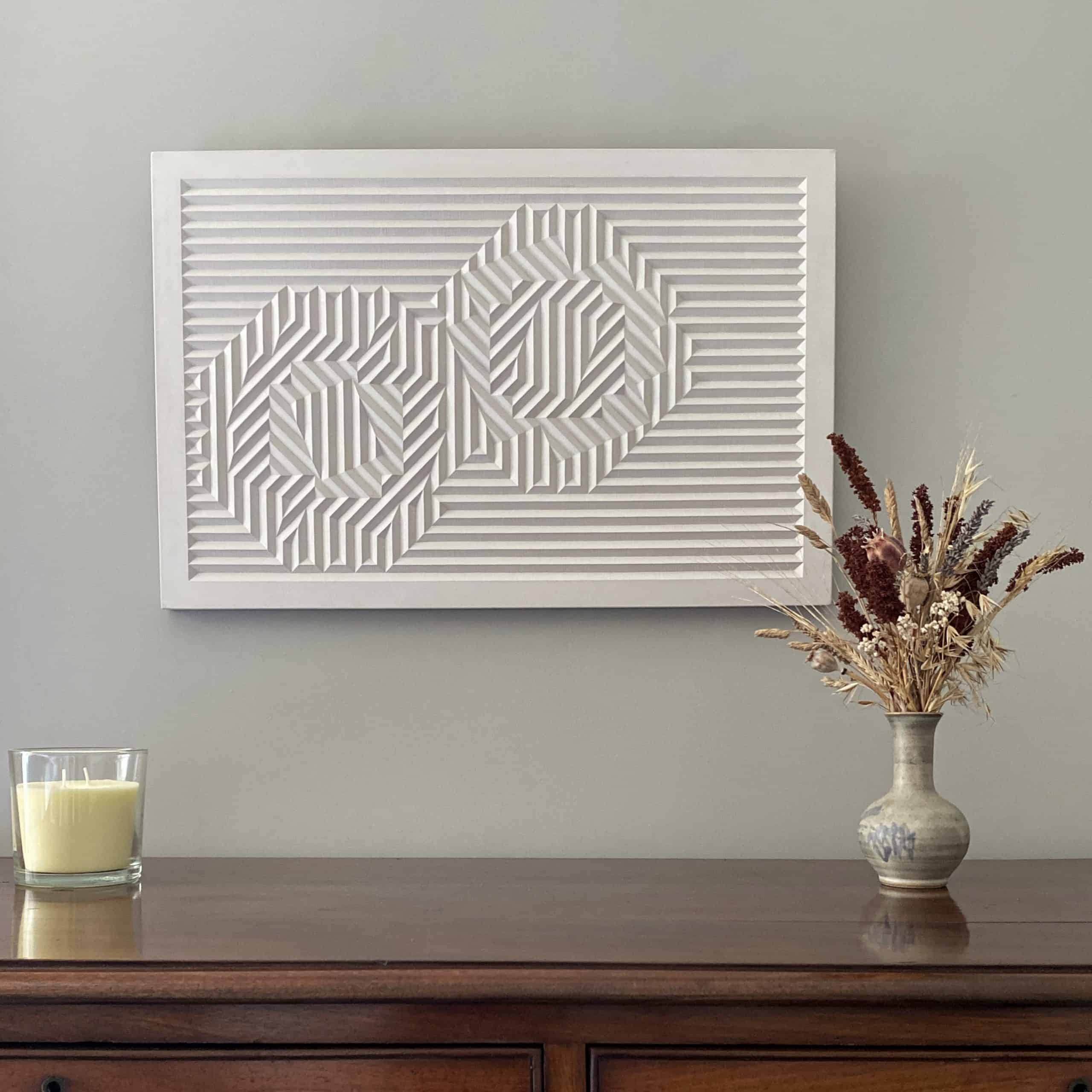 Light coloured cast of a geometric carving hanging on the wall above a chest of drawers
