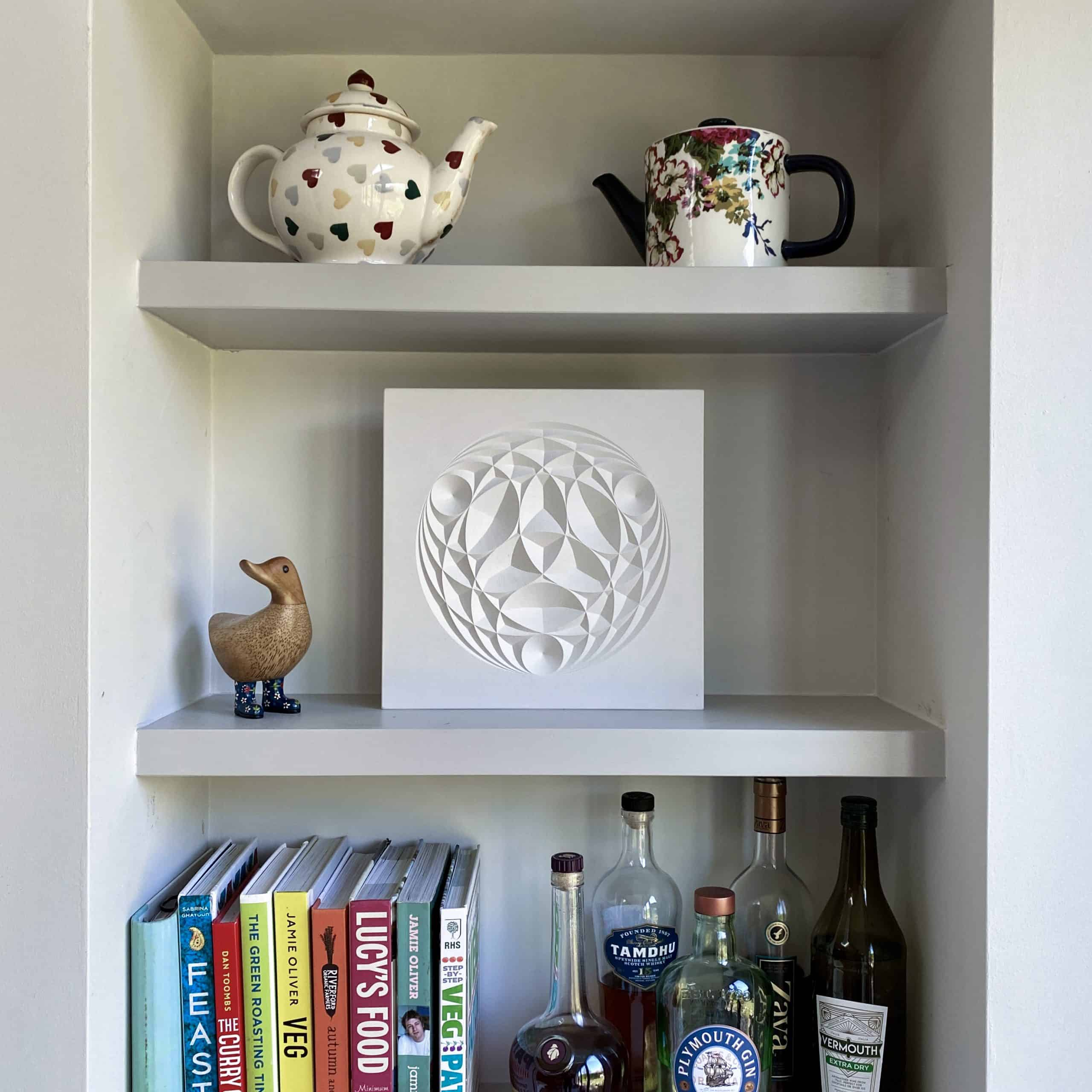 Light coloured cast sitting on a kitchen shelf with tea pots and recipe books