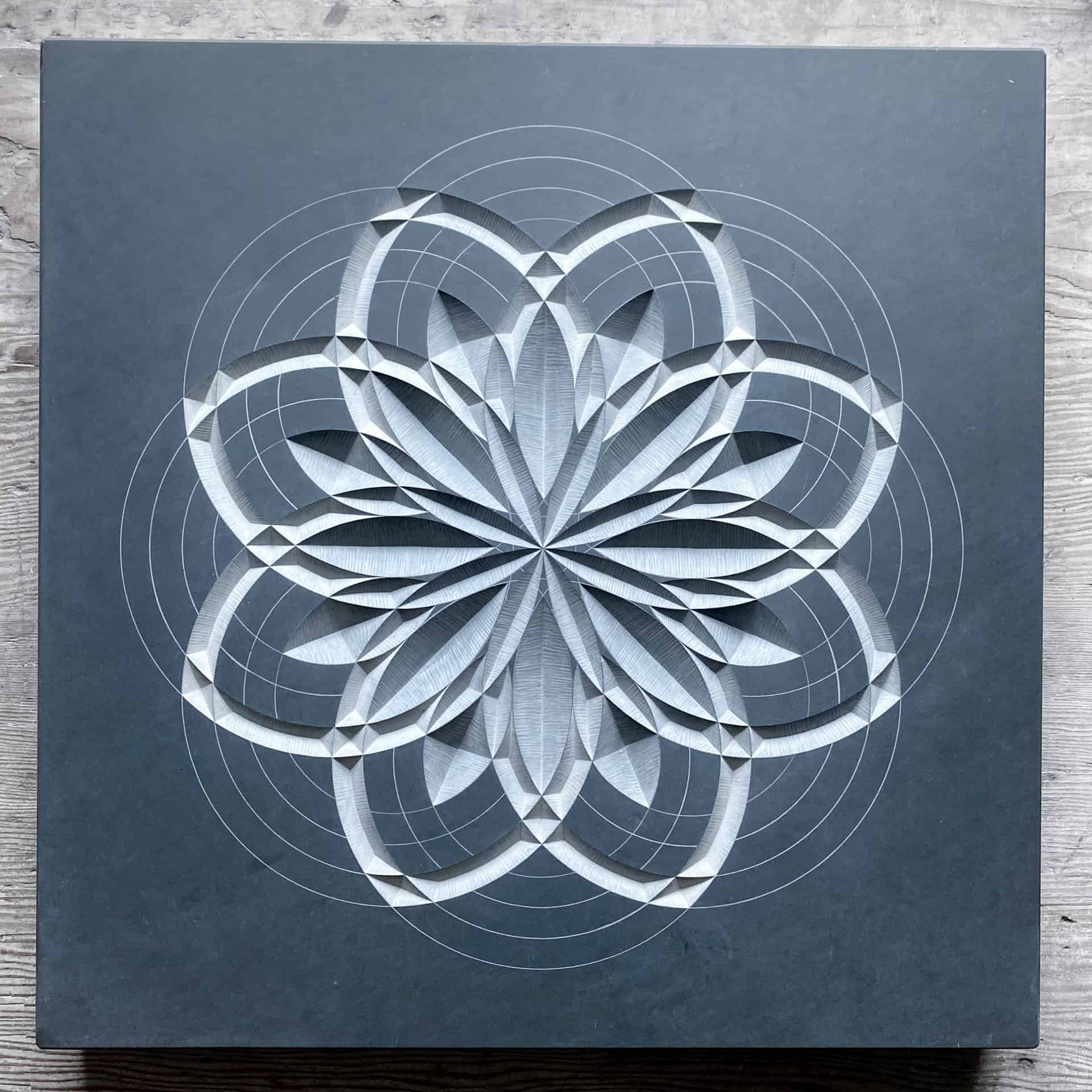 Dark grey Slate carving of a geometric pattern which looks like a flower
