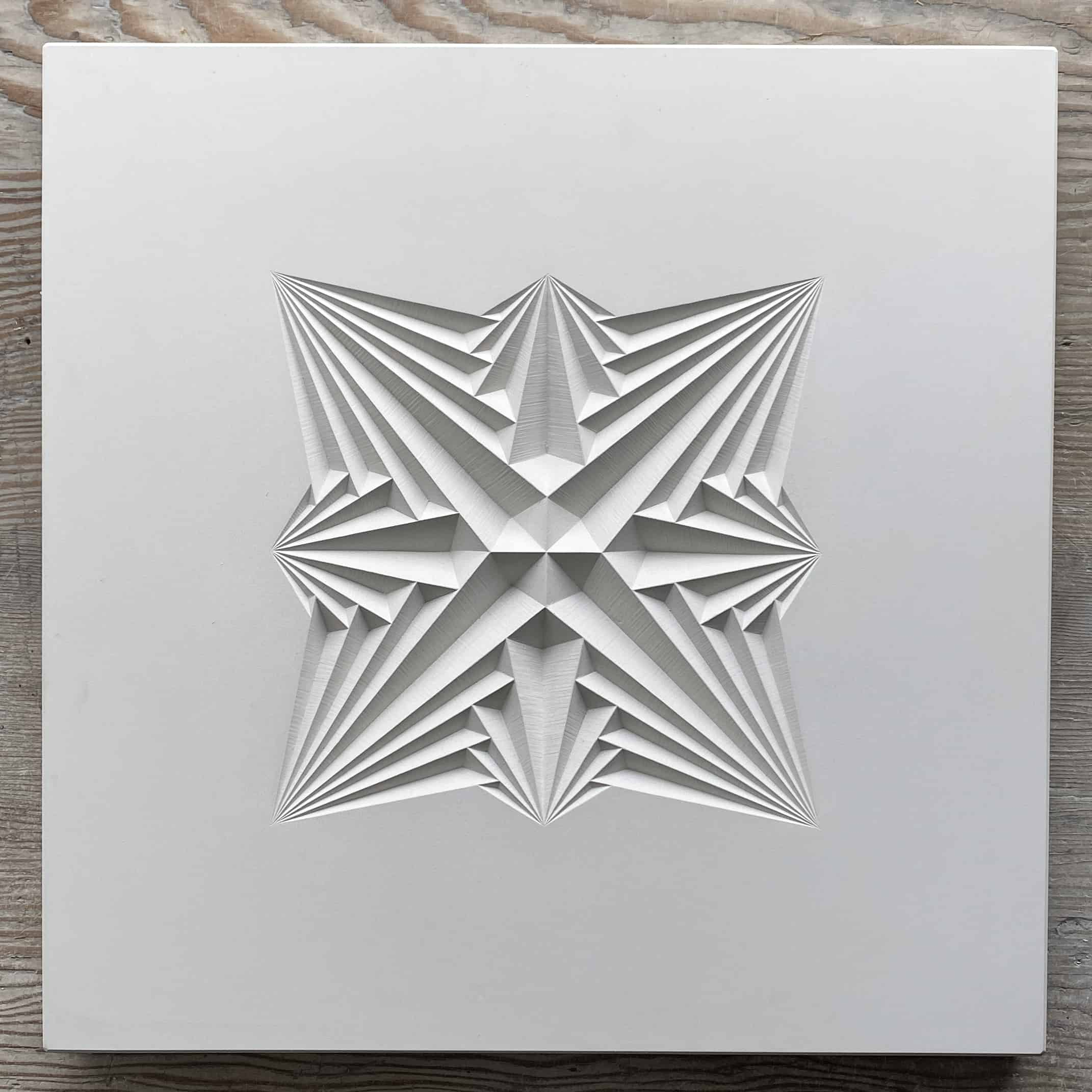 Light coloured cast of geometric carving