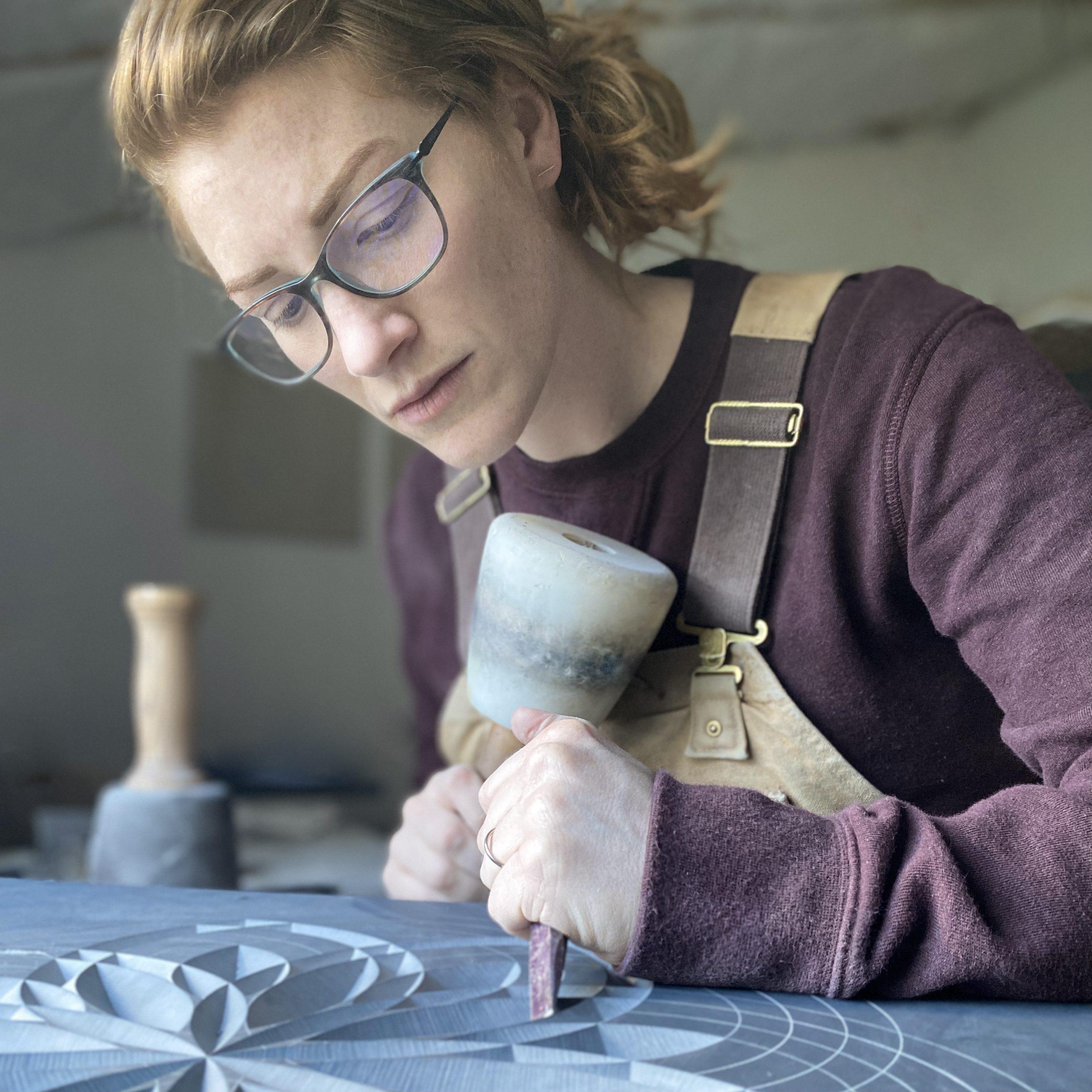 Portrait of Zoë carving in her workshop