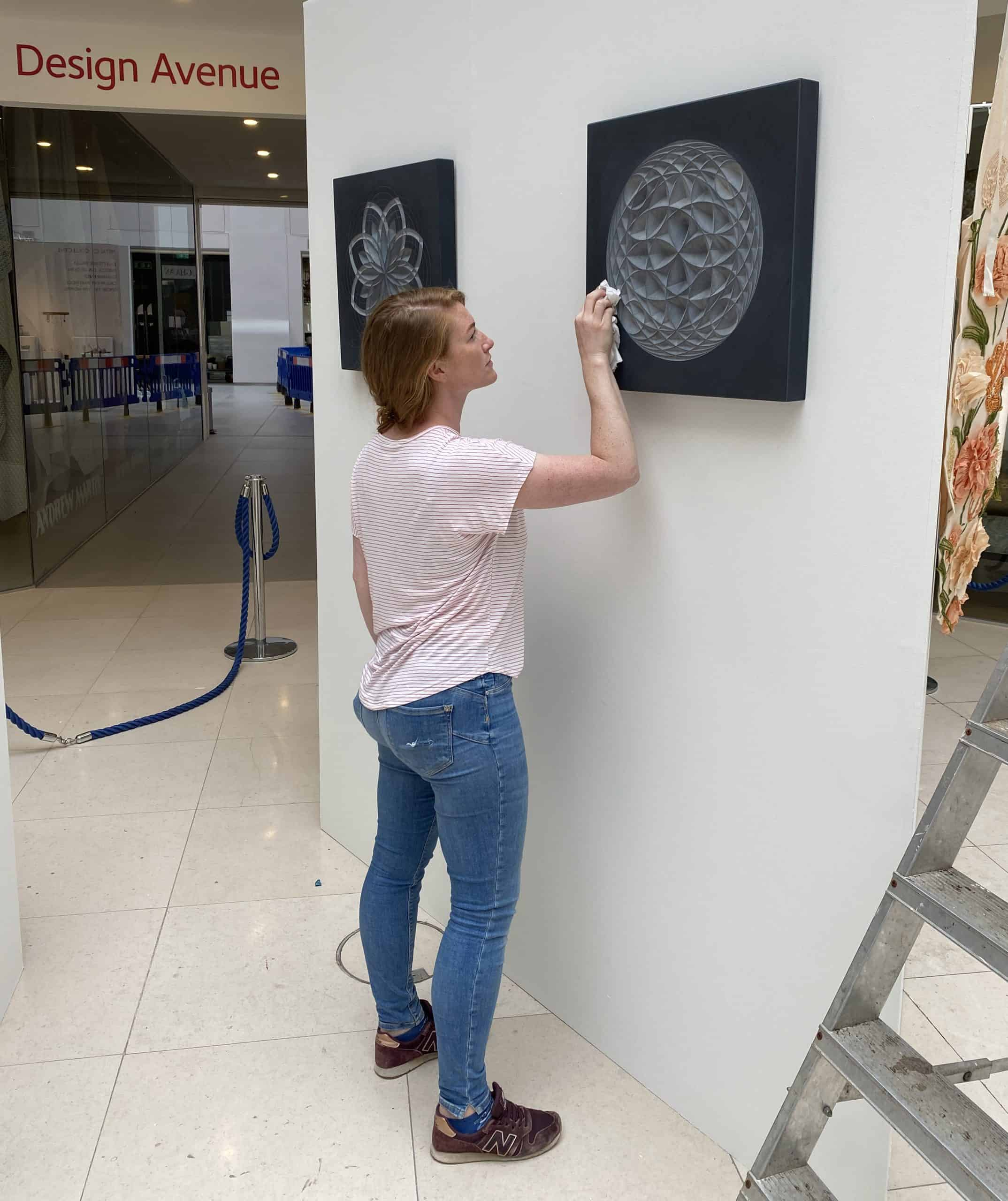 Zoe standing cleaning her work in a gallery before the show opens